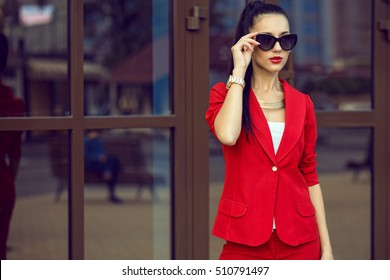 Portrait of young gorgeous dark-haired businesswoman in stylish sunglasses and bright red suit standing at the entrance of office building with mirrored windows. Outdoor shot. Copy-space