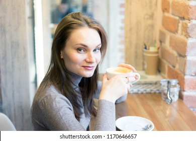 Portrait of young gorgeous female drinking tea and thoughtfully looking out of the coffee shop window while enjoying her leisure time alone, nice business woman lunch in cafe during her work break