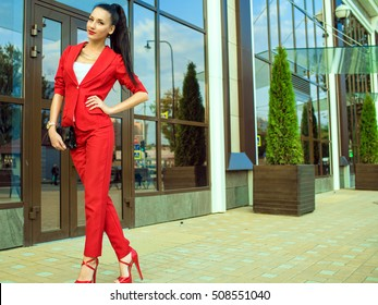 Portrait of young gorgeous lady with high pony tail in red costume and high-heeled shoes in front of mirrored shop windows holding a black handbag. Female fashion concept. Outdoor shot. Copy-space