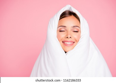 Portrait of young gorgeous smiling lady covered wrapped in blanket, closed eyes. Isolated over pink pastel background