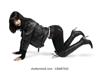 Portrait of young goth woman in lace-up boots over white
