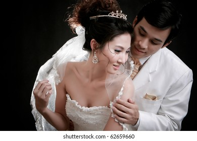 Portrait of young groom looking his bride from backside in erotic emotion at black background