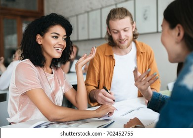 Portrait of young group of people working together in office. Group of students studying together in classroom. Two pretty girls happily talking and discussion something together