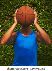 Portrait young guy basketball player with ball and swet tank top after training opposit green bush