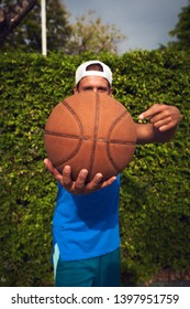 Portrait young guy basketball player in hat with ball and swet tank top after training opposit green bush