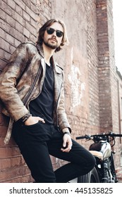 portrait young guy with a beard and mustache with sunglasses posing on the street vintage man, fashion men, hipster street casual motorcycle