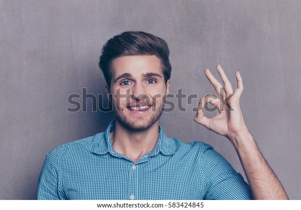 Portrait of young guy in checkered blue shirt showing hand gesture OK