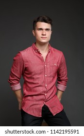 portrait of a young guy in a red shirt, isolated on a gray background.