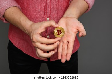 portrait of a young guy in a red shirt and a bitcoin coin in his hands, isolated on a gray background.