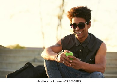 Portrait of young guy sending message with smartphone. Black african american male texting on his smart phone outdoors