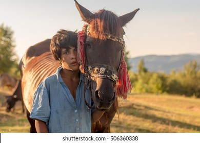 Portrait of young gypsy boy, herdsman, with his horse. Carpathian mountains, Ukraine.