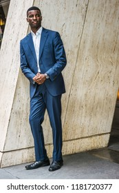Portrait of Young Handsome African American Businessman in New York, wearing blue suit, white undershirt, leather shoes, wristwatch, standing by column on street outside office, waiting, looking.