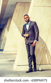 Portrait of Young Handsome African American Businessman with beard in New York, wearing black suit, leather shoes, standing by column on street, under sunshine, looking forward. Filtered effect.