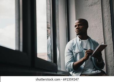 Portrait of young handsome african american man looking at window and writing notes