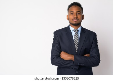 Portrait of young handsome African businessman in suit with arms crossed