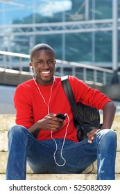 Portrait of young handsome african man using mobile phone, listening to music and smiling while sitting outdoors on steps