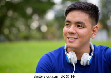 Portrait of young handsome Asian man relaxing at the park in Bangkok, Thailand