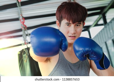 Portrait of a young handsome asian man practicing boxing on a punching bag at the sport club