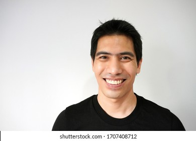 Portrait of a young handsome Asian man smile sincerely showing his teeth. Isolated on a light grey background. Studio concept of an attractive, charming, happy, positive, confident smiling male model