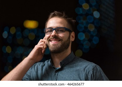 a portrait of a young, handsome and attractive man talking on the phone, smiling.