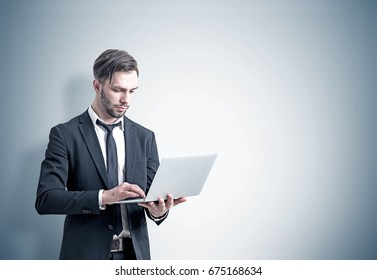Portrait of a young and handsome bearded businessman in a suit holding a laptop and working. Concept of success. Gray backgound. Mock up