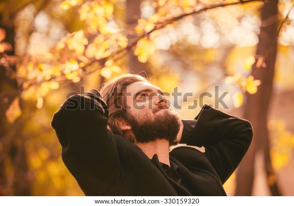 Portrait of young handsome bearded guy in the autumn city park. Enjoying of the moment of happiness.
