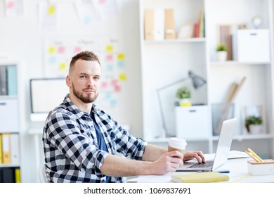 Portrait of young handsome bearded man in checked shirt looking at camera while sitting at laptop with coffee in modern office