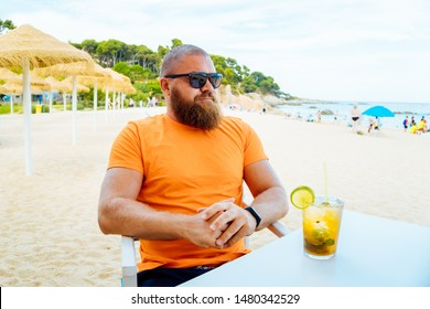 Portrait of young handsome bearded man sitting in a beach cafe or chiringuito with a glass of fresh mojito cocktail
