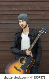Portrait of the young handsome bearded man with guitar on the wooden background. With shallow depth of field.