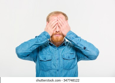 Portrait of young handsome blond bearded male in jeans shirt with eyes covered by hands over white background