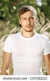 Portrait of a young handsome blond guy in a white T-shirt on a summer meadow at sunset. Attractive unshaven man