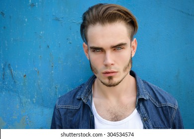 Portrait of young handsome blue-eyed man looking at camera outdoor against grunge obsolete wall