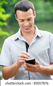 Portrait of young handsome brunette man wearing grey shirt holding phone and stylus and laughing at summer green park.