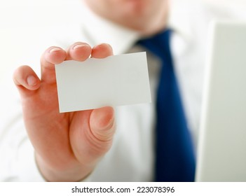 Portrait of young handsome business man holding blank white business card.