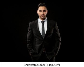 Portrait of young and handsome business man looking on you   isolated on black background