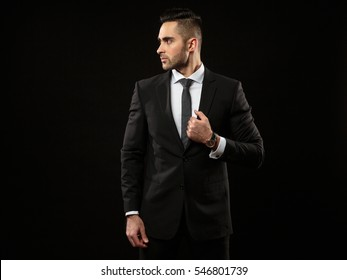 Portrait of young and handsome business man  isolated on black background