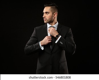 Portrait of young and handsome business man correcting a tie  isolated on black background