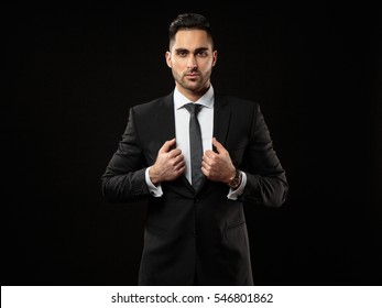 Portrait of young and handsome business man holding a jacket  isolated on black background