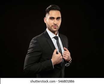 Portrait of young and handsome business man correcting jacket  isolated on black background