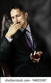 portrait of young handsome business man with Old Brandy Glass in hand and smoking cigar on black background. men's club
