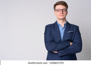 Portrait of young handsome businessman with eyeglasses crossing arms
