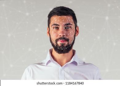 Portrait of a young handsome businessman on a black background. Biometric verification, face concept