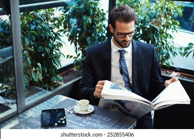 Portrait of a young handsome businessman reading a newspaper at his breakfast in coffee shop, brunette business man holding open newspaper sitting in cafe