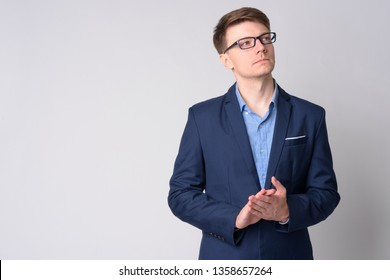 Portrait of young handsome businessman in suit thinking