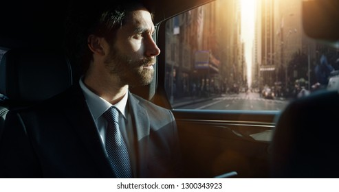 Portrait of young handsome businessman traveling in a modern car with a driver in center of the city by day. Concept of business, success, traveling, luxury