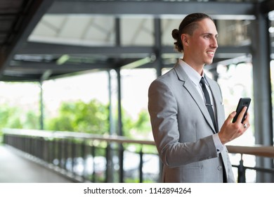Portrait Of Young Handsome Businessman Using Phone Outdoors