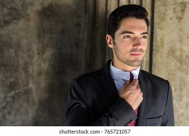 Portrait of young handsome businessman wearing suit exploring the city of Bangkok Thailand