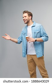 Portrait of young handsome caucasian man in jeans shirt over light background holding cup of coffee to go