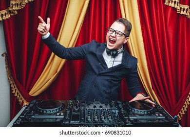 Portrait of young handsome charismatic Dj in formal suit standing at mixer and smiling at camera. Fashion and nightclubbing concept