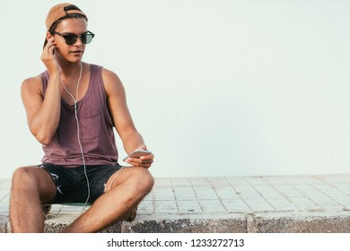 Portrait Of Young Handsome cheerful guy in sunglasses with headphones, sitting on a roadside in front of facade of residential building.